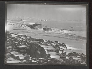"""View of Cape Evans from the Ramp, Cape Evans, October 1911  (""""View of snow covered rocky landscape with hut in the centre ground. Various items of equipment around the hut."""")."""