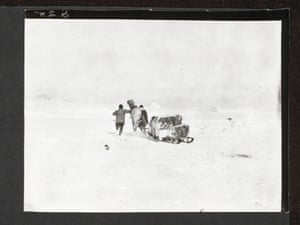 """Henry Bowers and Anton Omelchenko chasing Victor, Cape Evans, (""""Two men running beside a pony which is pulling a laden sledge on the snow. Group are running away from the camera."""")."""