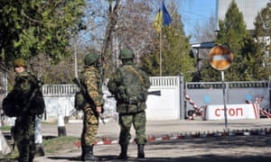 Armed men in military fatigues block access to Ukrainian military barracks in the small Crimean city of Bakhchisaray.