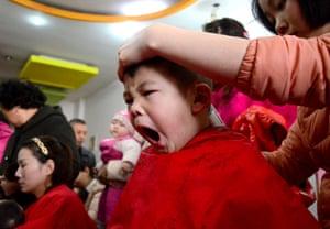 A child has their hair cut