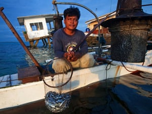 Lawag fisherman with catch in front of a house about to fall into the sea, the catch an eleven hour effort brought in two kilos, a total of 100 filipino pesos, Bilangbilangan Island, Danajon Bank, Central Visayas, Philippines.