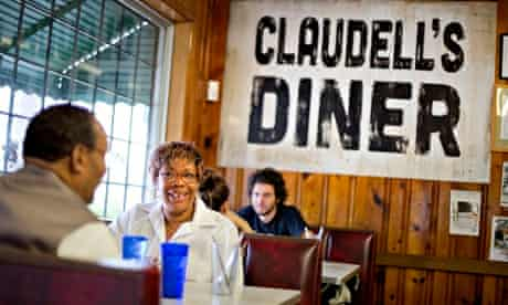 "Customers in the Home Grown restaurant sit in front of a sign left behind from the filming of ""Troub"