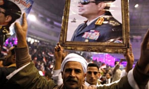 Supporters of Egypt's army chief Sisi hold posters during festivities in Cairo