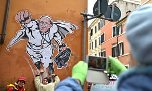 Children pose next to a street mural of Pope Francis as a superman