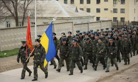Unarmed Ukrainian troops bearing their regiment and the Ukrainian flags march to confront soldiers under Russian command occupying the Belbek airbase in Crimea in Lubimovka, Ukraine.