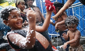 The Pereira family revels in fake snow while dancing during the 'Ceu na Terra' street carnival in Rio de Janeiro