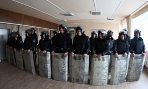 Policemen stand guard inside the regional state administration building in the eastern industrial city of Donetsk one day after it was occupied by some 300 pro-Russian demonstrators on 4 March, 2014.