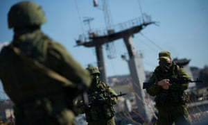Russian soldiers guard a pier where Ukrainian naval ships are moored in Sevastopol