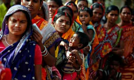Voter hold crying baby as she stands in queue to cast her ballot at Lalgarh village