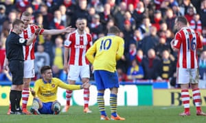Arsenal's Olivier Giroud on the ground after a challenge from Stoke's Charlie Adam, right.