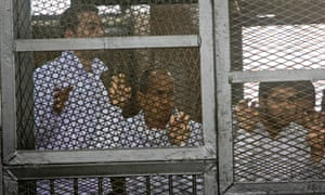 Al-Jazeera producer Baher Mohamed, left, and correspondent Peter Greste, centre, in the defendants' cage in a Cairo courtroom