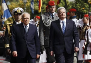 Greek President Karolos Papoulias (2nd L) escorts his German counterpart Joachim Gauck as they inspect a guard of honour at a welcome ceremony in Athens March 6, 2014.