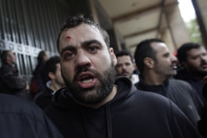 A protester, injured during clashes with riot police, shouts slogans during a demonstration against austerity measures in Athens, on Thursday March 6, 2014.