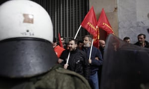 Protesters affiliated to the Communist Party shout slogans as riot policemen block them during a demonstration against austerity measures in Athens, on Thursday March 6, 2014.
