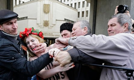 A Femen protester against Putin's policy concerning Ukraine is detained near Crimea's parliament