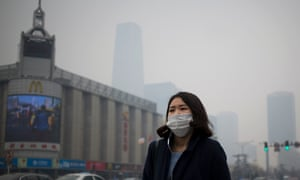 A Chinese woman wears a mask as she walks past the capital city skylines shrouded by pollution haze in Beijing in March 2014