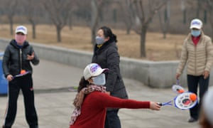 """residents wearing masks exercising in a park in smog-covered Beijing on 23 February as China's National Meteorological Centre issued a """"yellow"""" smog alert"""
