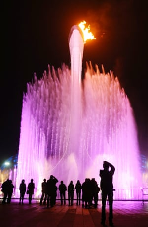 The Olympic cauldron is surrounded by fountains and coloured lights.
