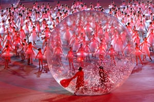 Ballerinas dance as a large plastic ball enters the arena.