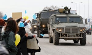 A Russian military convoy drives past anti-war protesters during a rally on a road in Simferopol