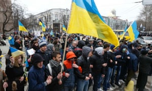 Pro-Ukrainian supporters carry Ukrainian flags as they march during a rally in Simferopol.