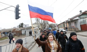 Pro-Russian supporters march with a Russian flag during a rally in Simferopol.