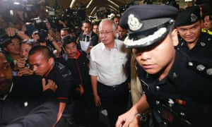 The prime minister, Najib Razak (centre), arrives to meet family and friends of passengers on board the missing Malaysia Airlines flight, at Kuala Lumpur International airport.