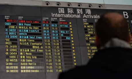 People stand beside the arrival board in Beijing showing the missing Malaysia Airlines flight