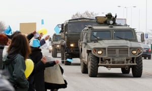 A Russian military convoy drives past pro-Ukraine protesters during a rally on a road in Simferopol, Crimea.