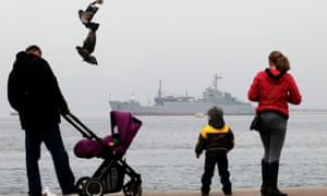 A family walks in front of Russian navy ship 'General Ryabikov' moored in the harbour of Sevastopol, Crimea.