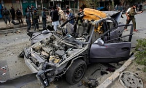 Police inspect the wreckage of a car destroyed in the bombing in Nangarhar province, Afghanistan.