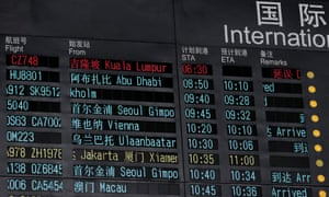 An information board indicating that flight MH370 of Malaysia Airlines is delayed, at Beijing Capital International Airport.