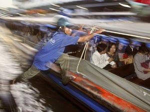 A fare collector jumps onto a motorised canal boat on the Khlong Saen Saep canal in Bangkok, Thailand.