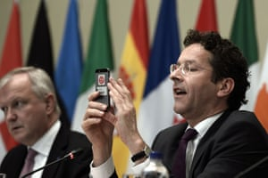 President of the Eurogroup an Finance Minister of the Netherlands Jeroen Dijsselbloem (R) takes a picture of the conference hall, flanked by Vice President of the European Commission Olli Rehn (L), during a press conference of the Eurogroup as part of the Informal Meeting of Ministers for Economic and Financial affairs at the Zappion Hall in Athens on April 1, 2014