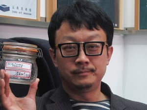 Beijing artist Liang Kegang poses with the jar of fresh air collected in Provence, France, in an art gallery in Beijing, China. The jar of air has fetched $860