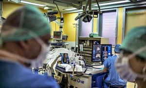 A surgeon sitting in front of screens of a Focal One device performs a prostate tumorectomy.