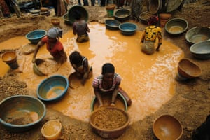 Prospectors pan for gold at a new gold mine found in a cocoa farm near the town of Bouafle, Ivory Coast.