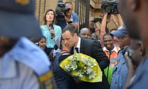 A woman hugs South African athlete Oscar Pistorius after handing him flowers as he leaves the North Gauteng Hight Court in Pretoria during his ongoing murder trial. The prosecution have accused Pistorius of tailoring evidence and overplaying his deep fear of crime to justify shooting dead his girlfriend Reeva Steenkamp.