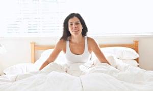 Smiling Hispanic woman sitting in bed