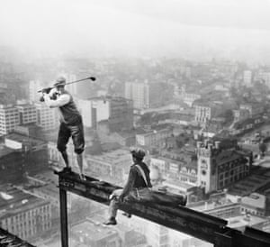 A cigarette smoking golfer and his caddy teeing off on the girder of a building under construction in Los Angeles in 1927.