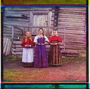 Three young women offer berries to visitors to their izba, a traditional wooden house, in a rural area along the Sheksna River, near the town of Kirillov, circa 1909.