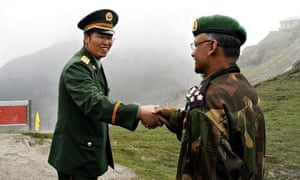 A Chinese army officer greets his Indian counterpart at the border between Sikkim state and Tibet