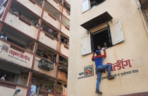 Window to window canvassing in the India General Elections. Independent candidate, Gaurav Sharma, wearing a 'spiderman' costume, climbs to the window of a residential building to speak to residents as he campaigns for the Lok Sabha elections in Mumbai.