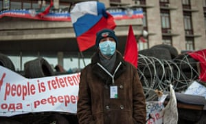 Pro-Russian protesters stand guard near the occupied regional administration building in Donetsk
