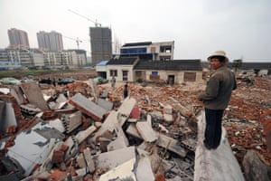 A worker looks out over rubble to 75-year-old Yao Baohua's house