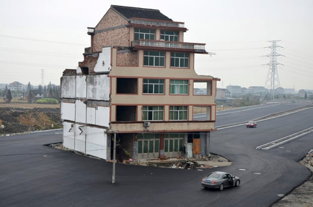 November 2012: Perhaps the most famous nail house - left in the middle of a newly built road in Wenling, Zhejiang province. An elderly couple refused to sign an agreement to allow their house to be demolished.