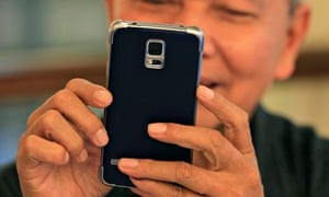 A man reacts while trying out his new Samsung Galaxy S5 in Jakarta