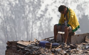 In the morning, a man sits on top of debris from the fire.