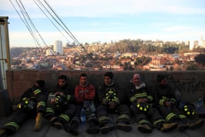 Firefighters take a break after a night fighting the fire.