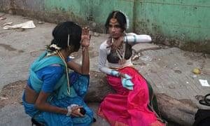 Indian transgender dancers put on makeup before a performance in Kolkata